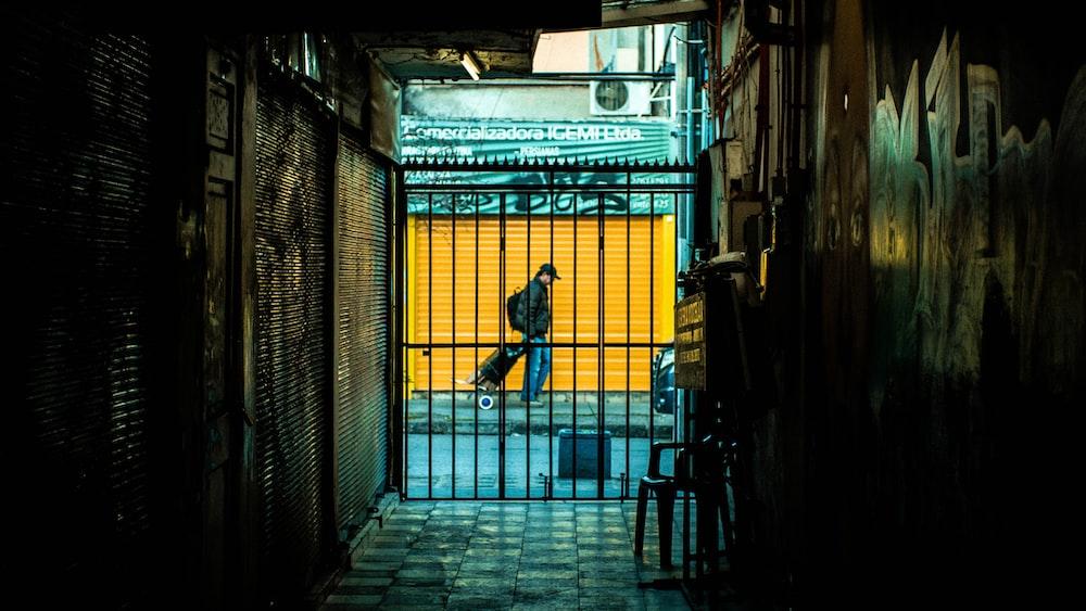 man pulling luggage while walking near pathway beside building