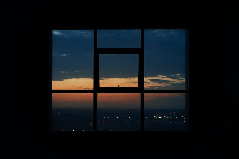silhouette photography of city view from a glass window