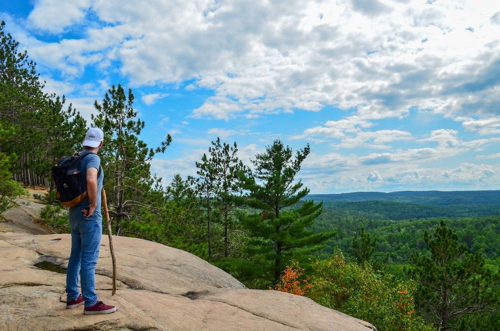 man wearing blue shirt and blue denim jean standing near trees during daytime