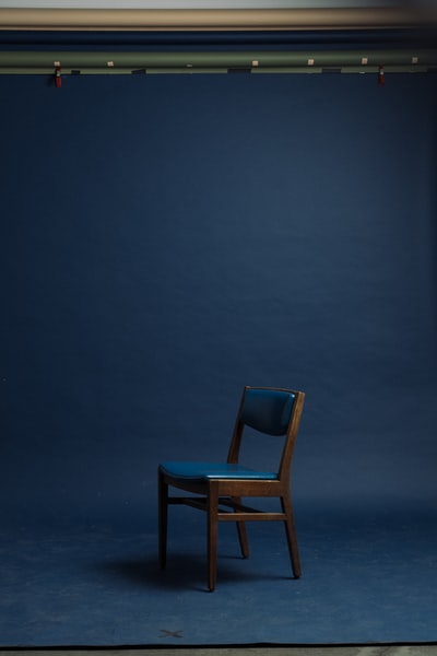 blue padded brown wooden armless chair