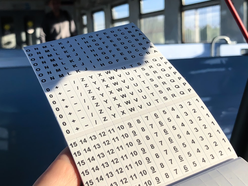 person showing white and black letters and numbers sticker paper
