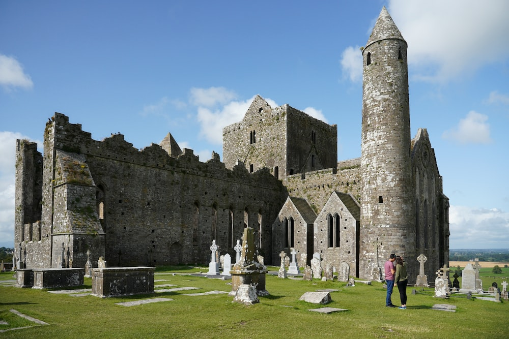 people standing near brown castle under blue sky and white clouds