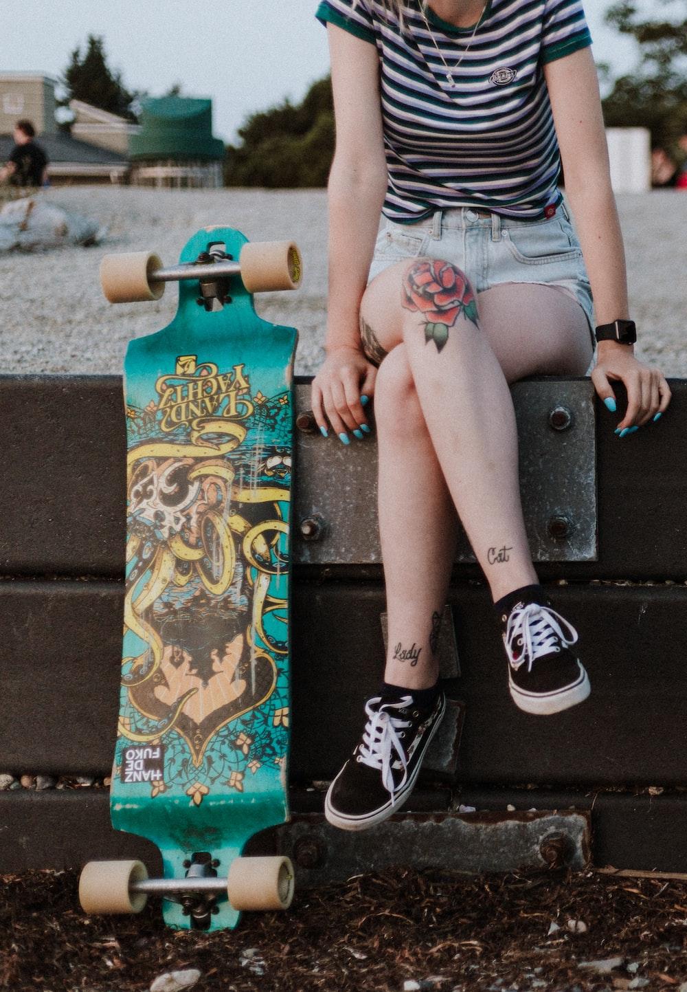 girl wearing green and white stripe shirt sitting besides green longboard