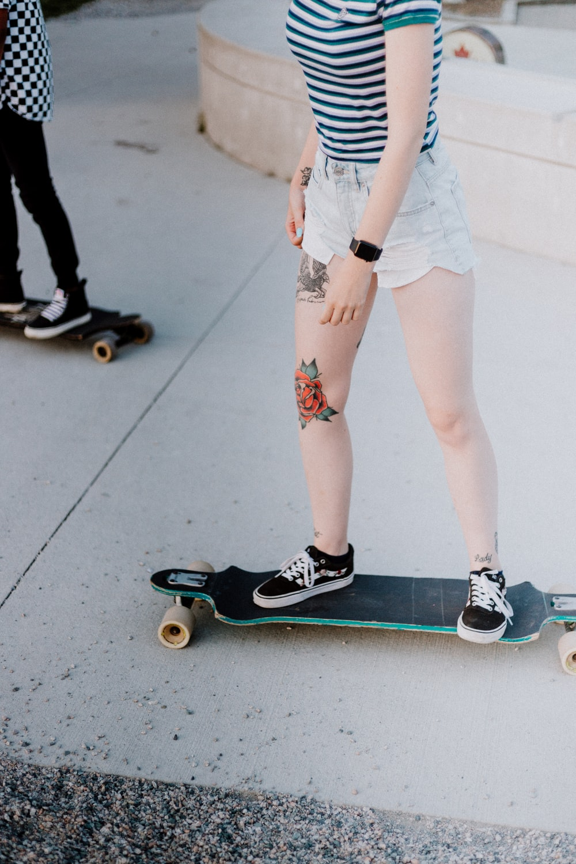 woman riding longboard on pathway