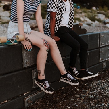 two person sits on fence