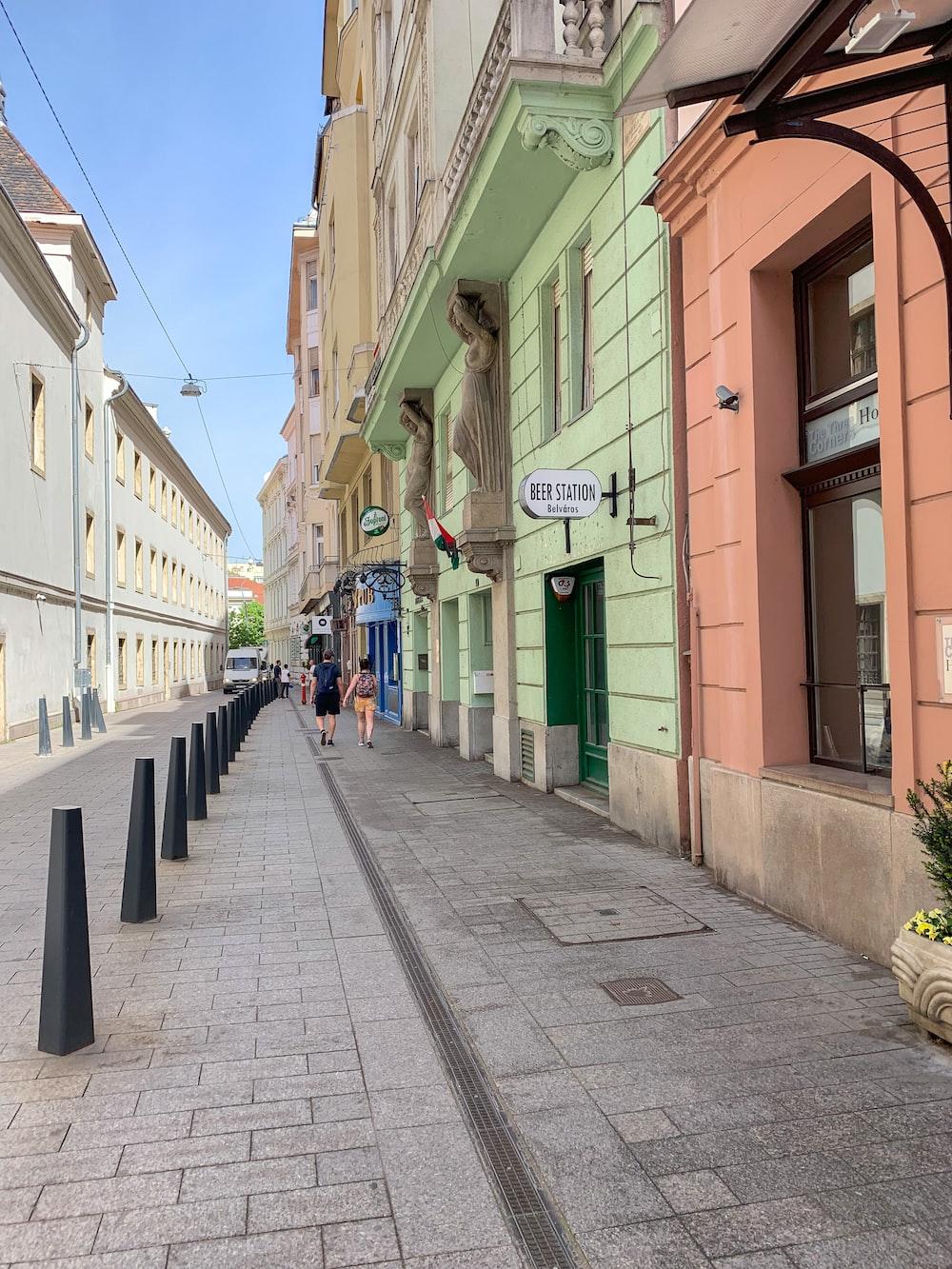 two person walking between buildings