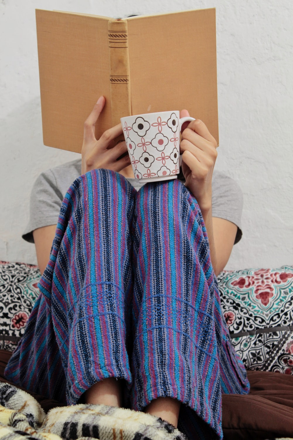person covering face with book