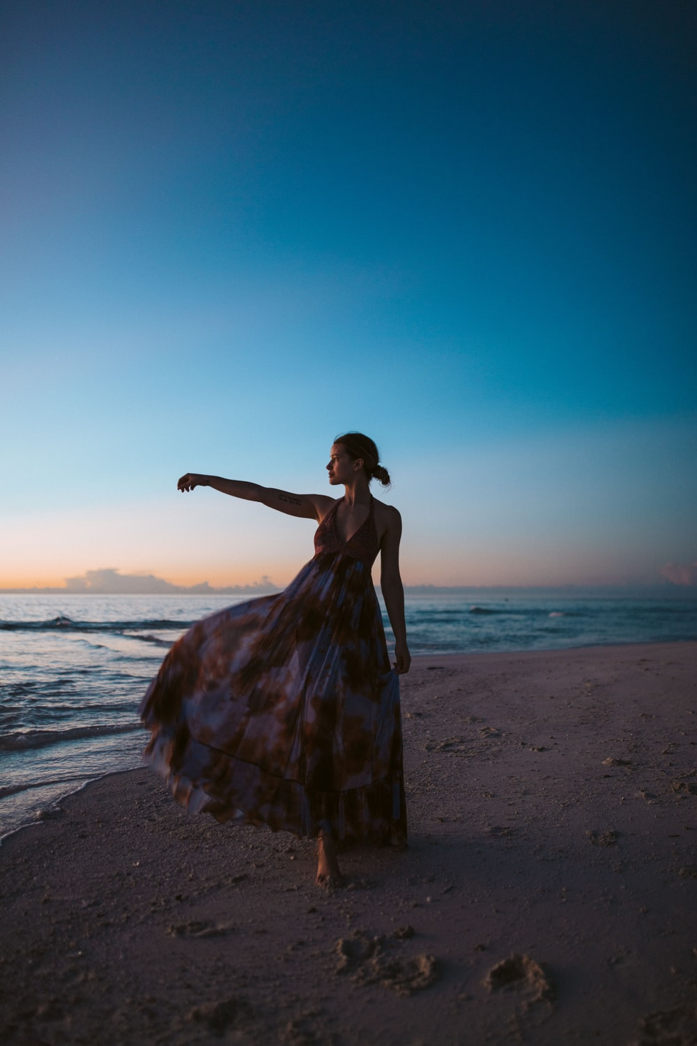 women's white and brown floral long dress standing beside body of water during golden hour