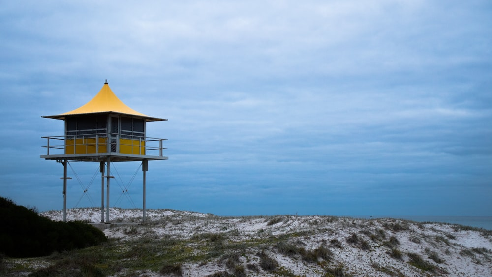 yellow and white lifeguard house under blue and white skies