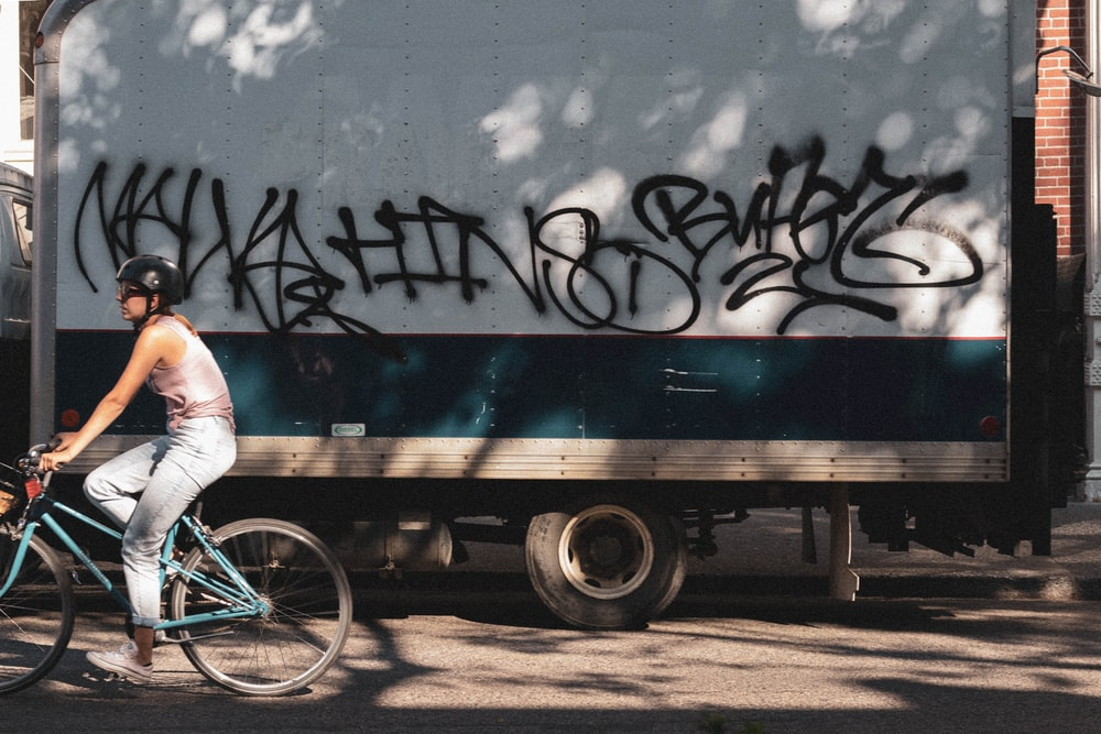 girl wearing pink tank top riding bicycle besides gray delivery truck
