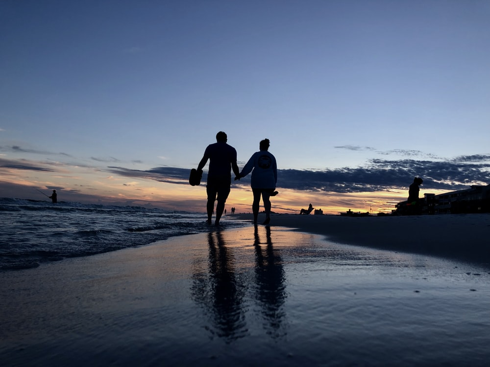 silhouette photography of two people walking on seashore