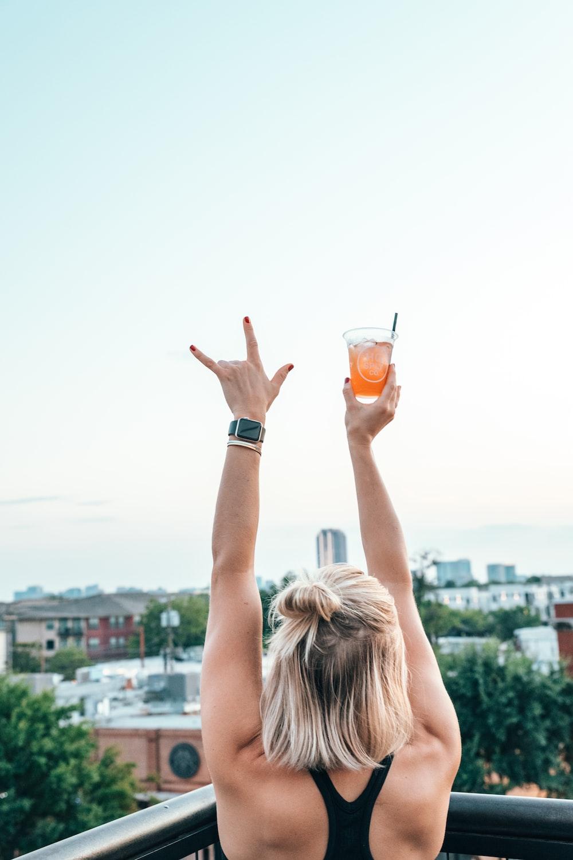 woman raising hand holding drinking glass