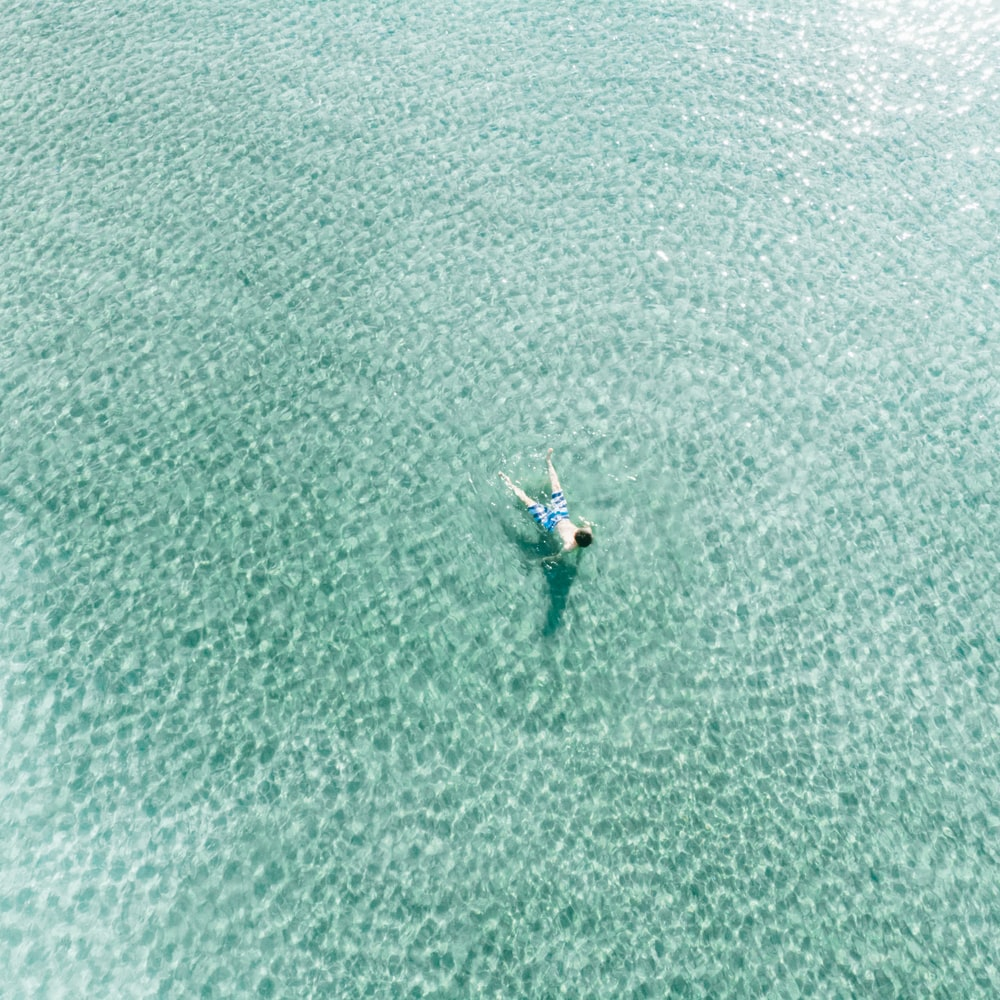 aerial photography of man in body of water during daytime