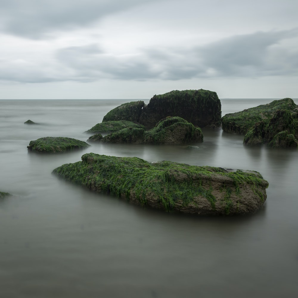 rock formations on sea under white skies