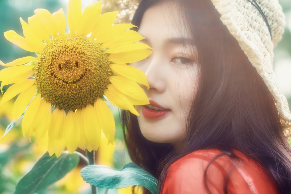 woman standing close to yellow smiling sunflower