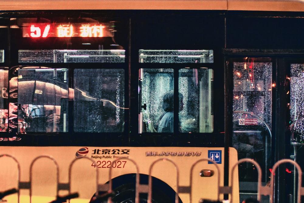 woman sitting inside orange and black bus