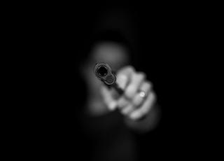grayscale photography ofperson holding gun