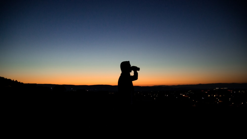silhouette photo of man about to drink