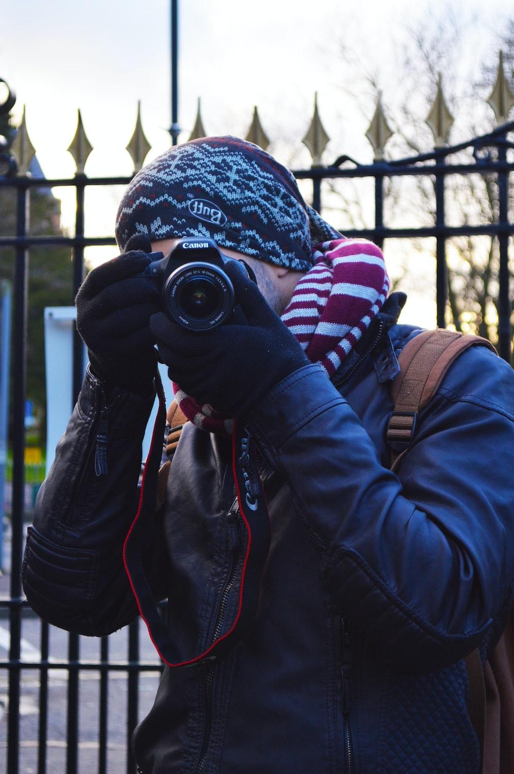 man wearing black jacket using black Canon DSLR camera near black metal gate