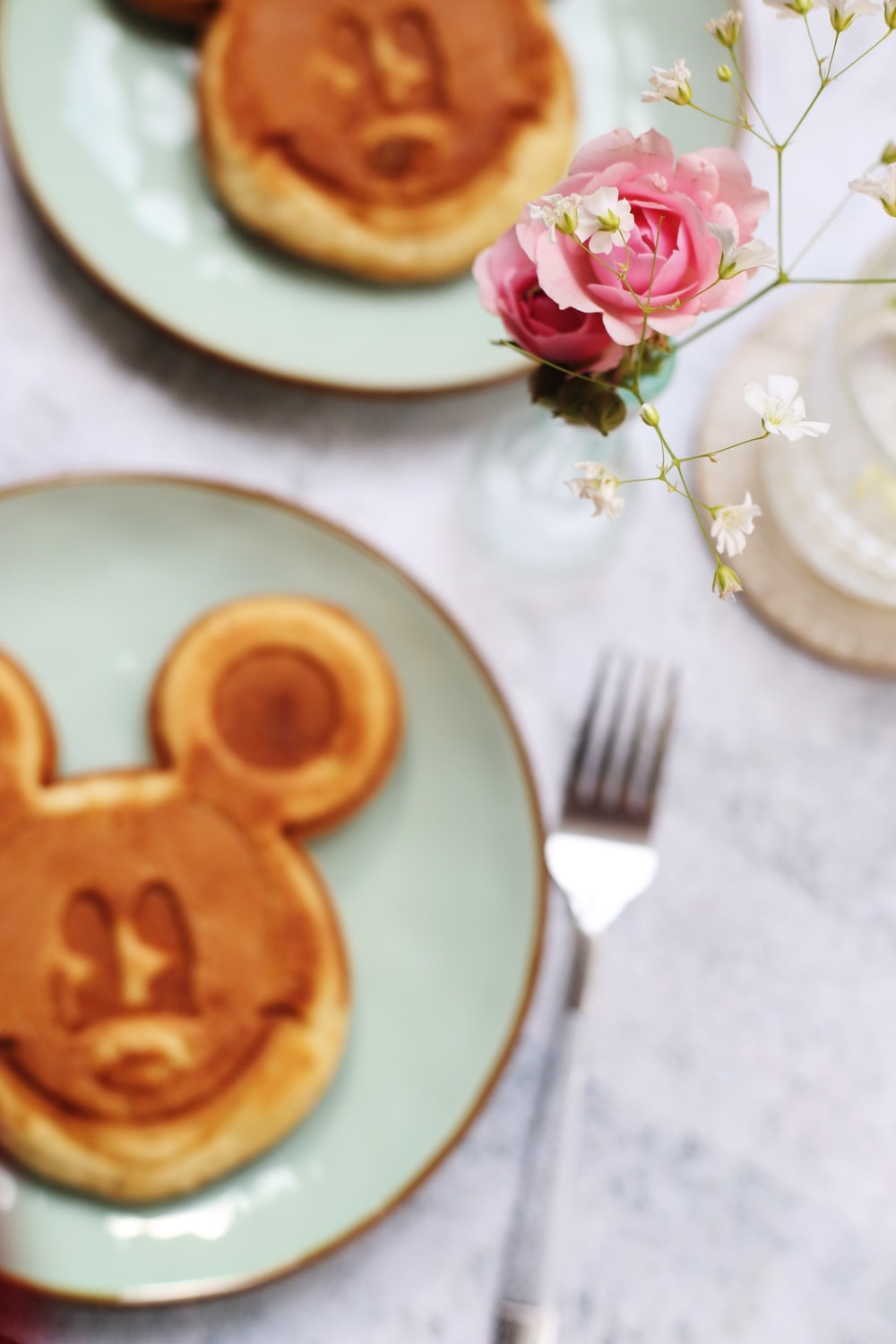 two plates of Mickey Mouse face pancakes on table