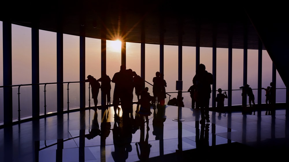 silhouette of standing people viewing through glass wall during golden hour