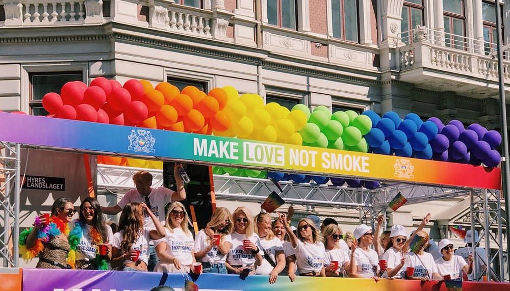 women lining up in rainbow colored make love not smoke platform with balloons