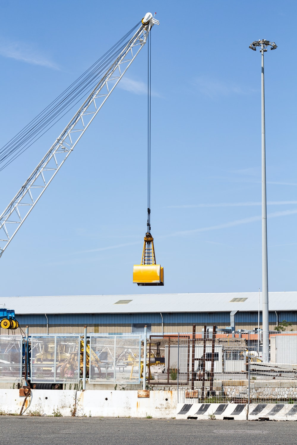 crane holding yellow box over building during daytime
