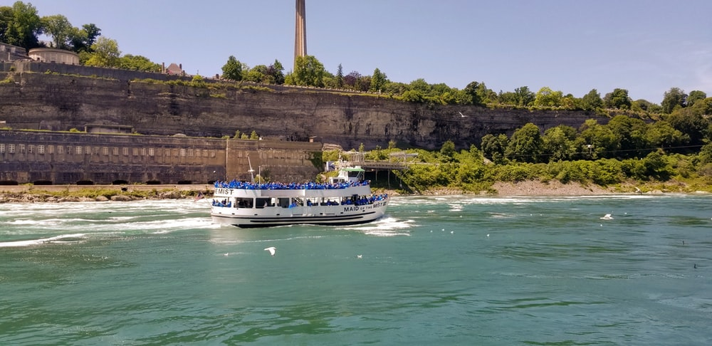 white and blue boat at the river during daytime