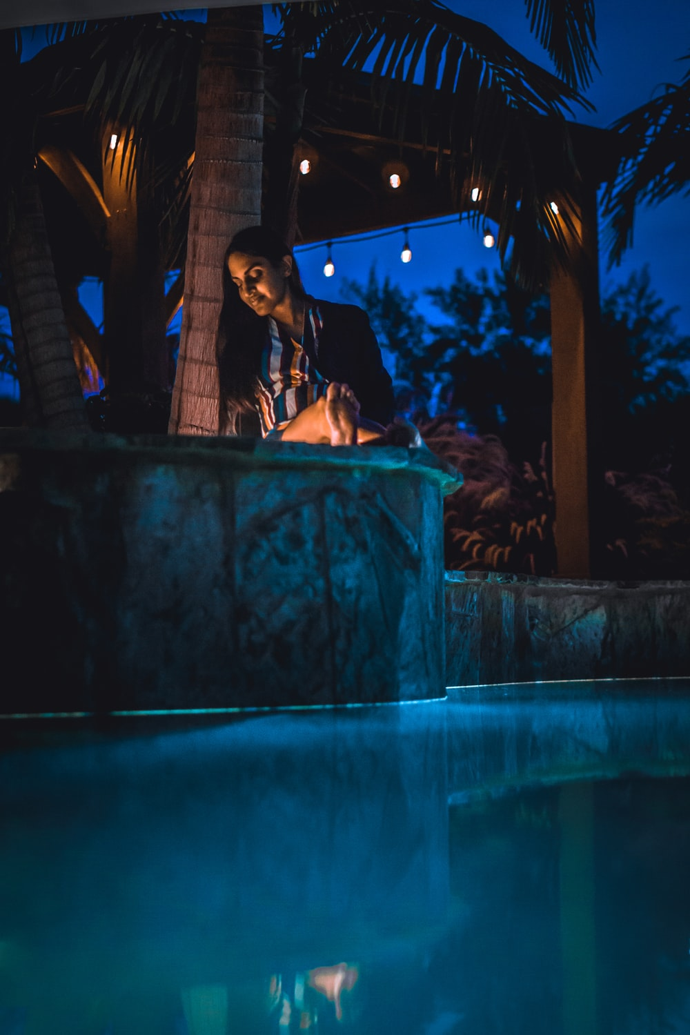woman sitting in pool beside lighted pendant bulbs during night time