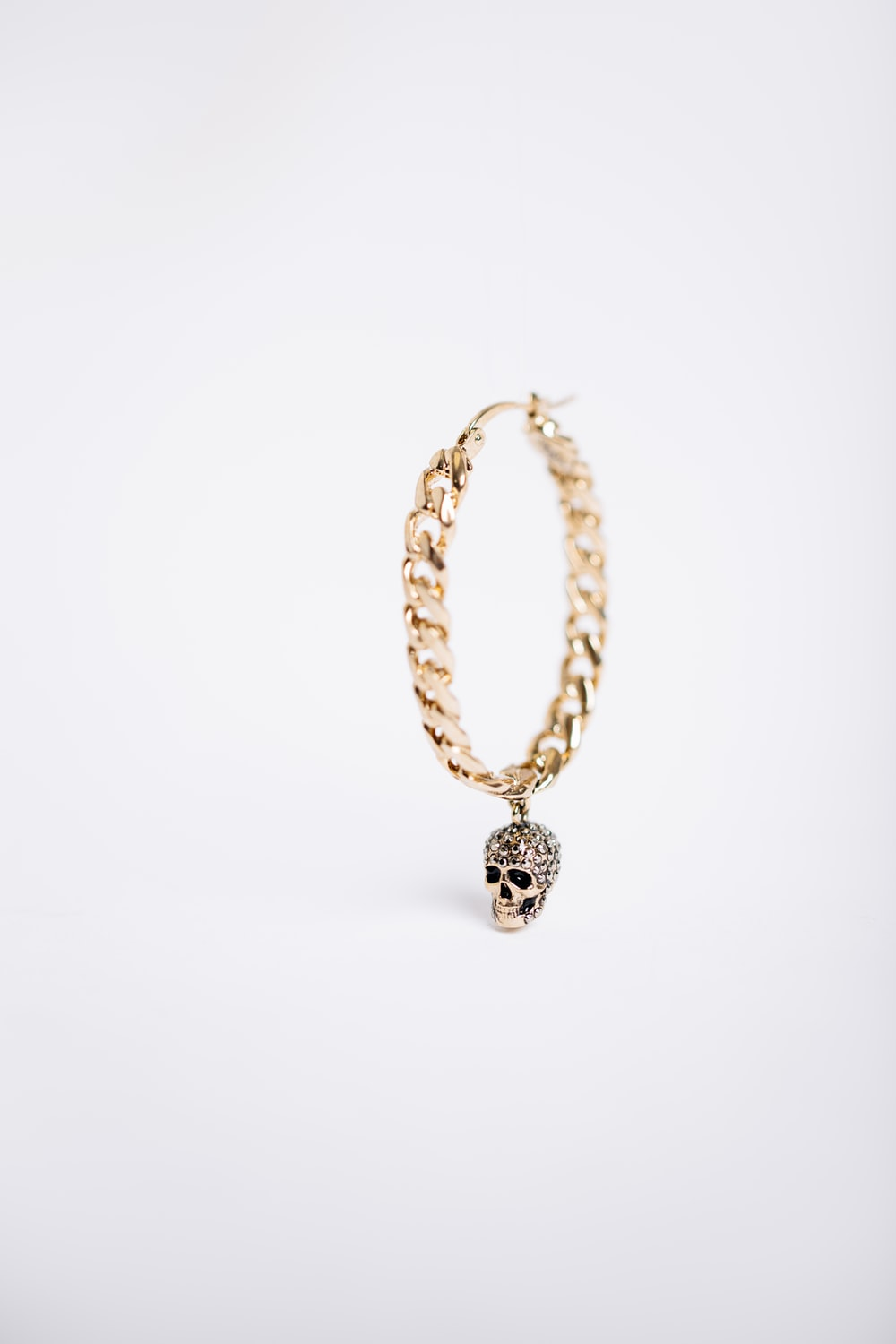 gold-colored skull charm earring