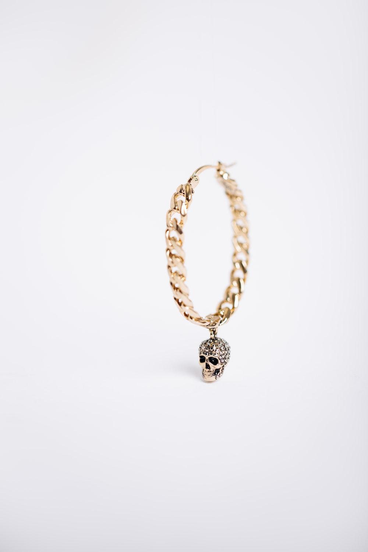 gold-colored skull charm earring