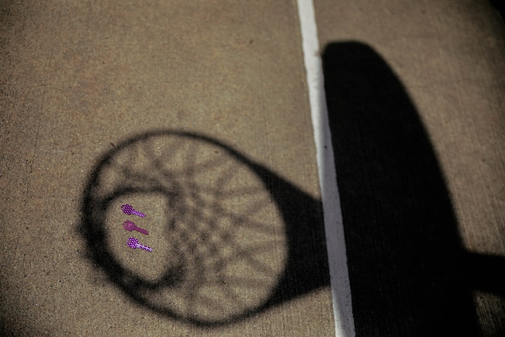 shadow of basketball system on gray pavement surface