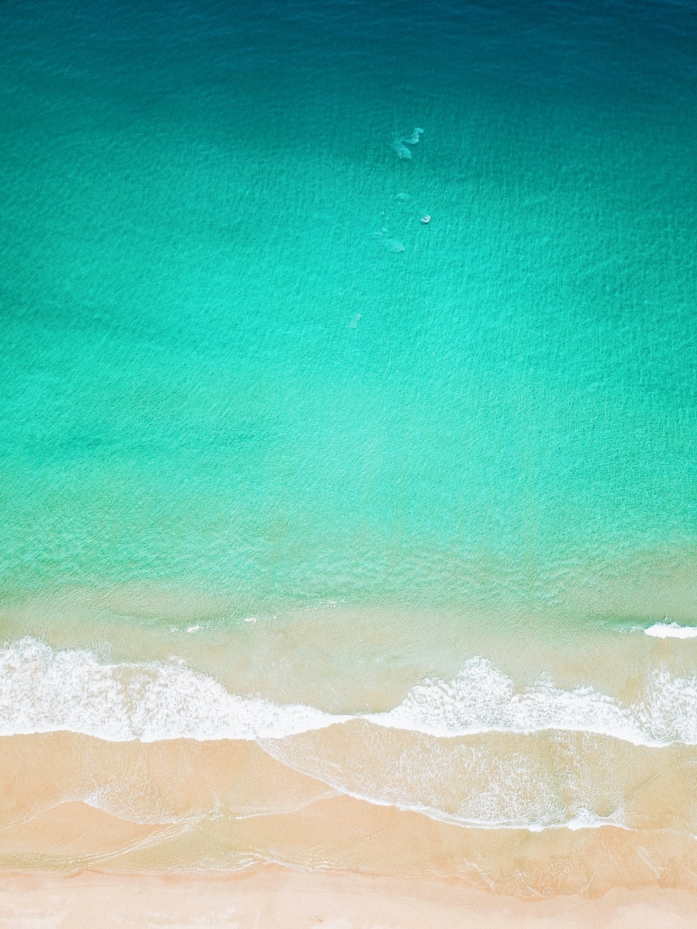 aerial photo of seashore clear green water