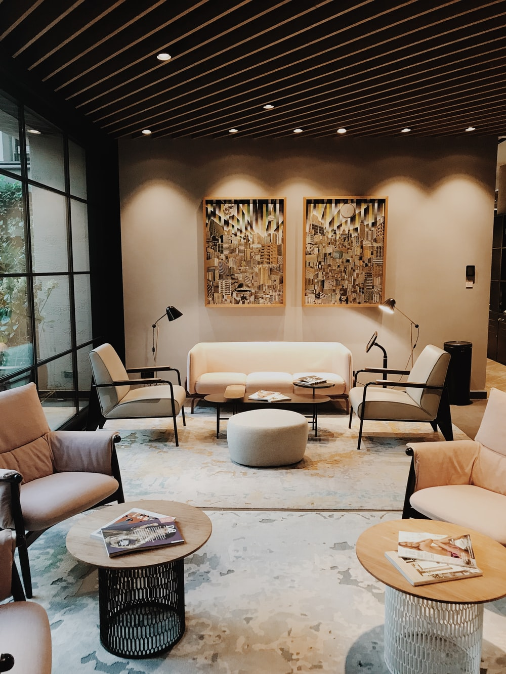 部屋の中に置かれる黒い金属によって組み立てられるベージュのパッドを入れられたソファー