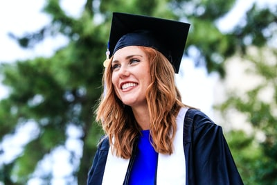 woman wearing academic gown graduation teams background