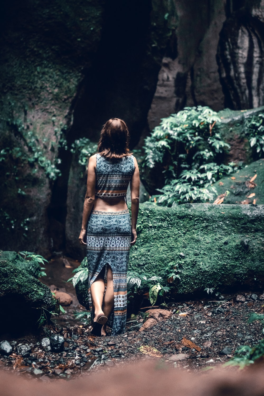 woman walking towards cave