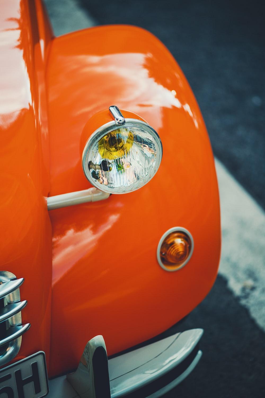 classic orange vehicle on road