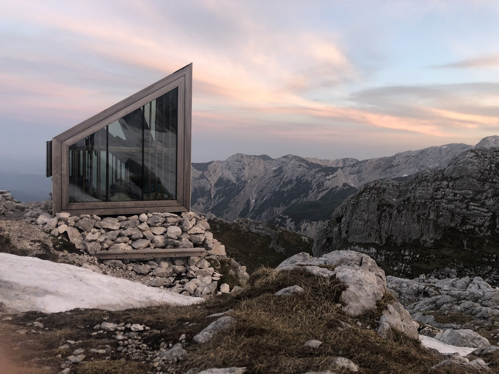 white-framed glass cabin on top of a mountain