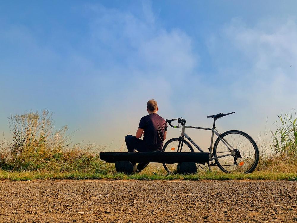 man sitting near white bicycle