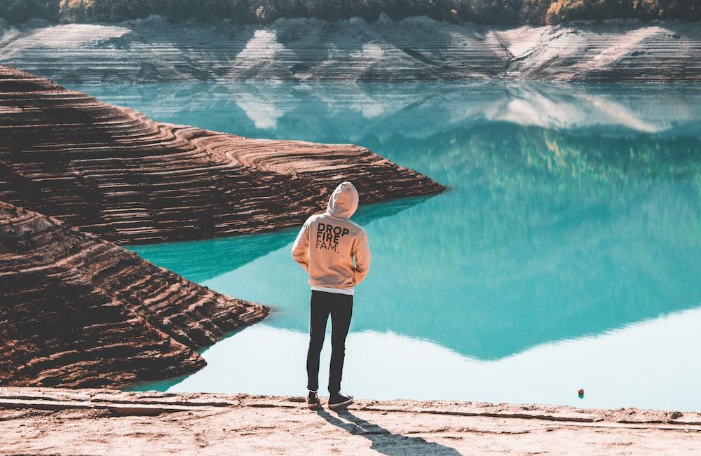 person wearing brown hooded jacket standing near blue ocean