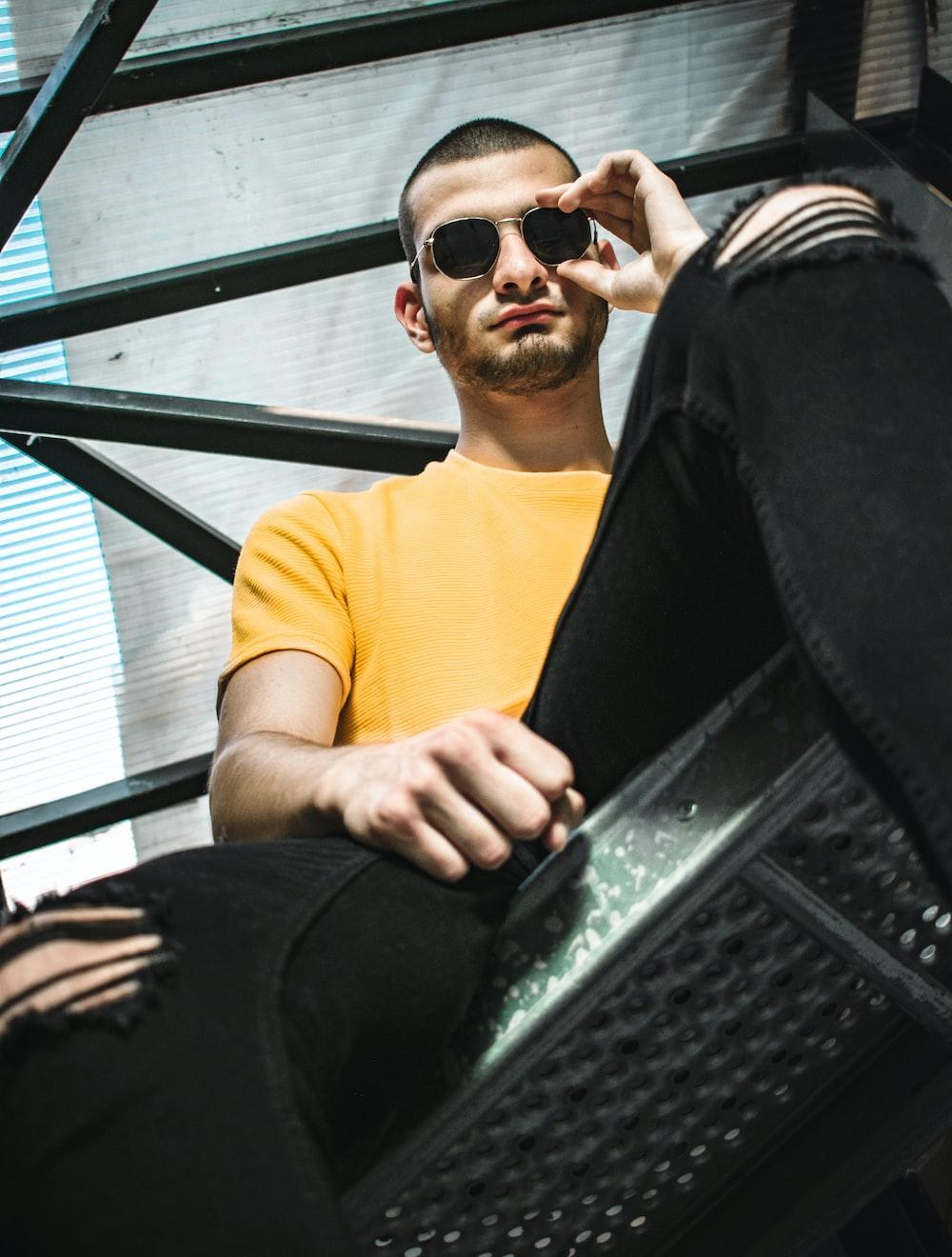 man in yellow shirt sitting on meta