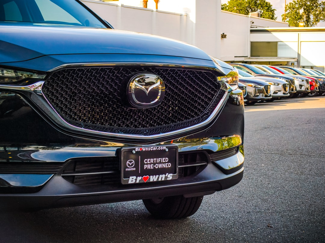 A 2020 Mazda CX-5 partied in a dealership parking lot during sunset.
