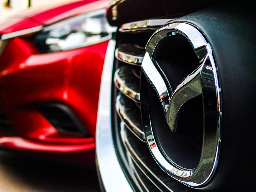 Mazda emblem on grille beside parked red car