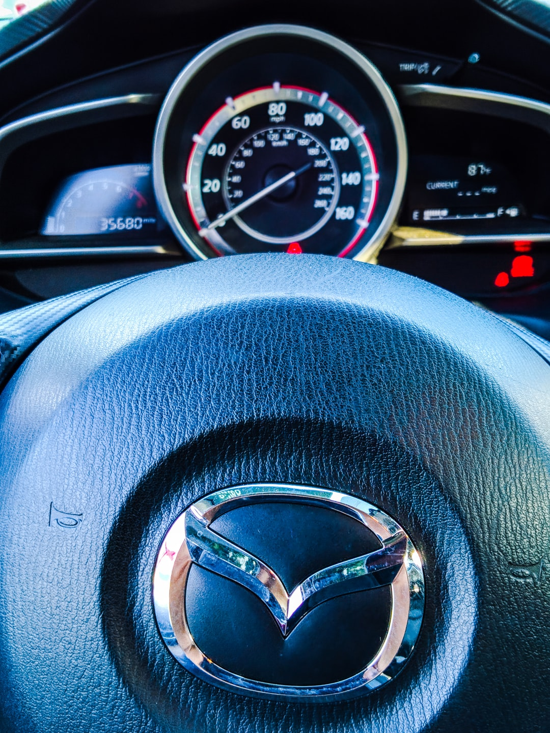 Closeup of a Mazda steering wheel and tachometer.