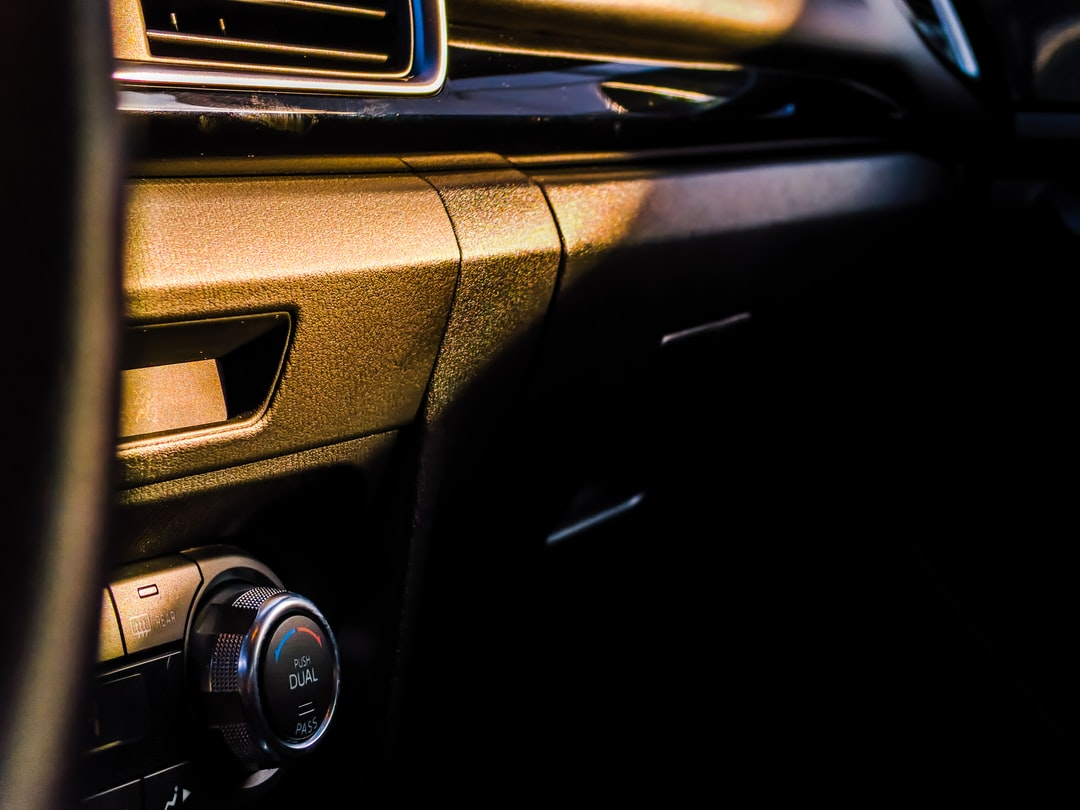 The interior of a car showing air vents and the glove compartment during sunset