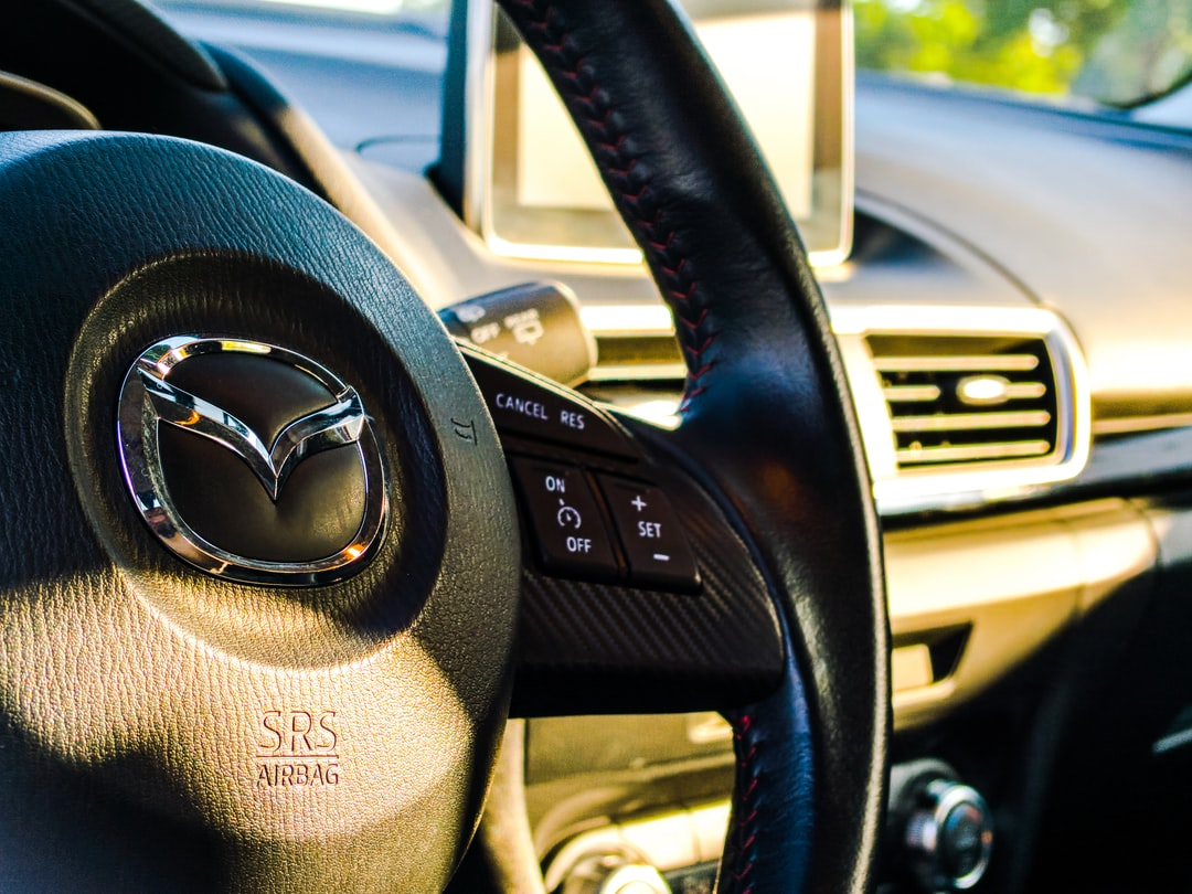 The black interior leather of a Mazda during sunset.