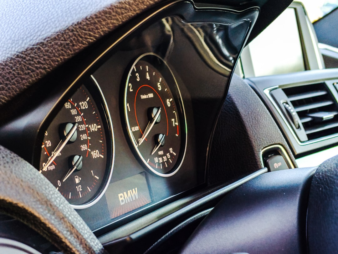 The interior of a BMW 3 Series on a sunny day with the focus on the tachometer