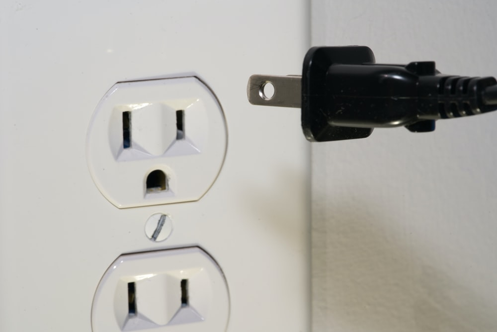 black male plug in front of electric socket