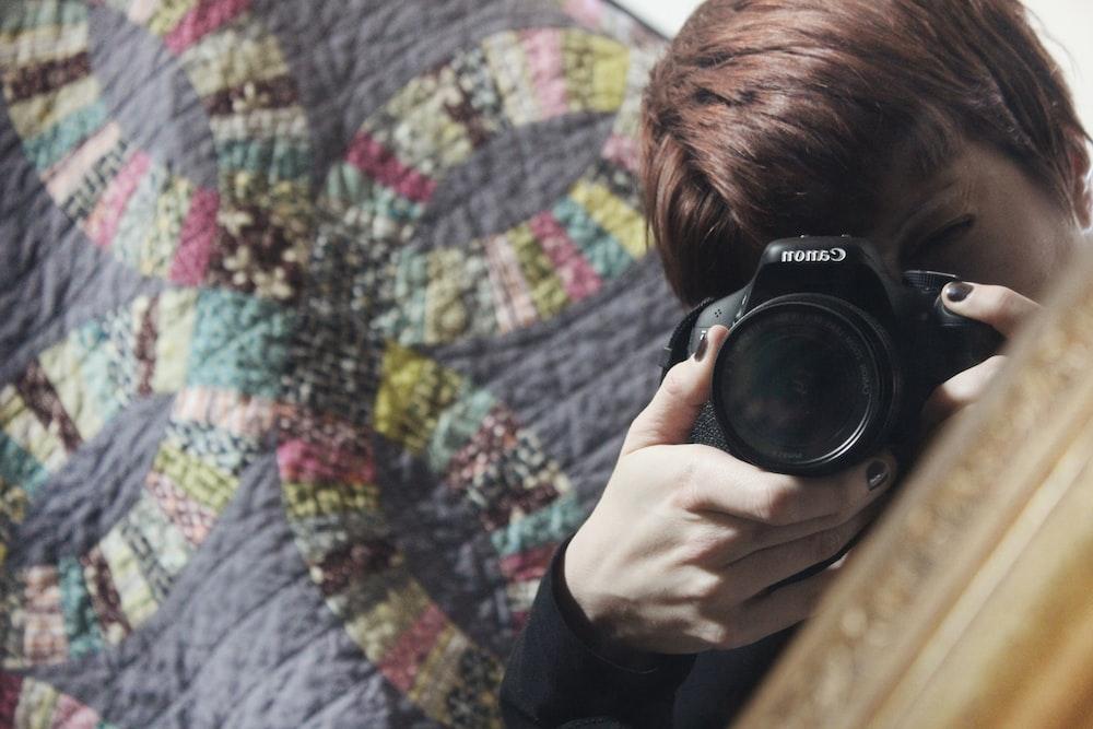 person using black DSLR camera