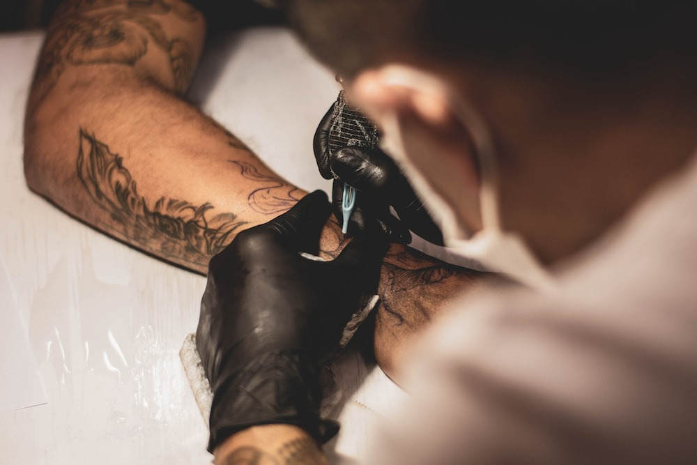 shallow focus photo of person tattooing person's right arm